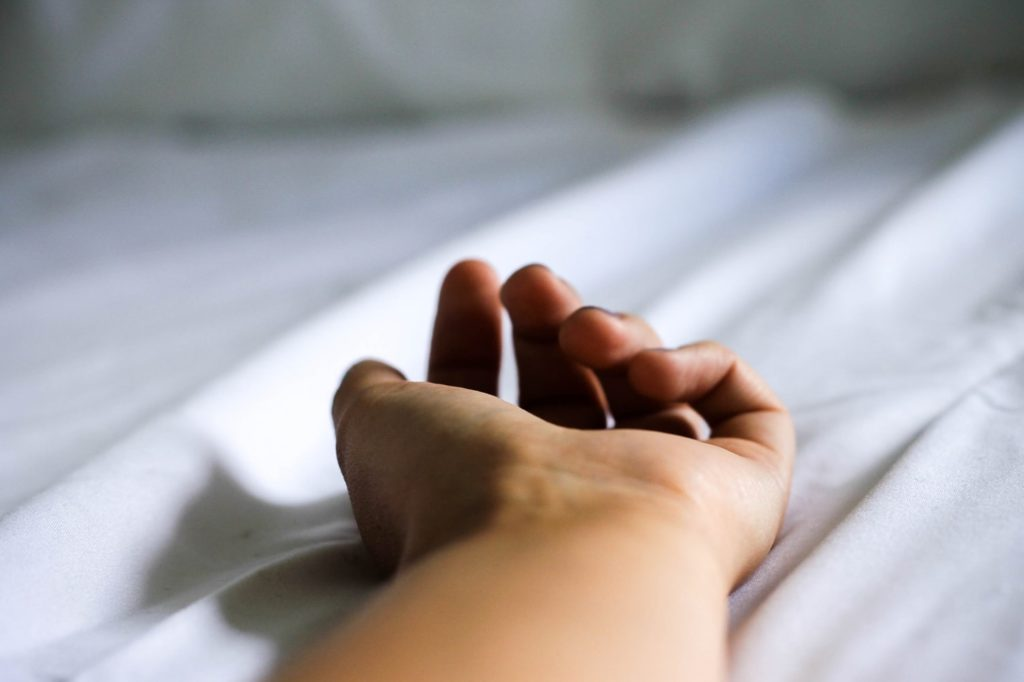 une main sur un lit